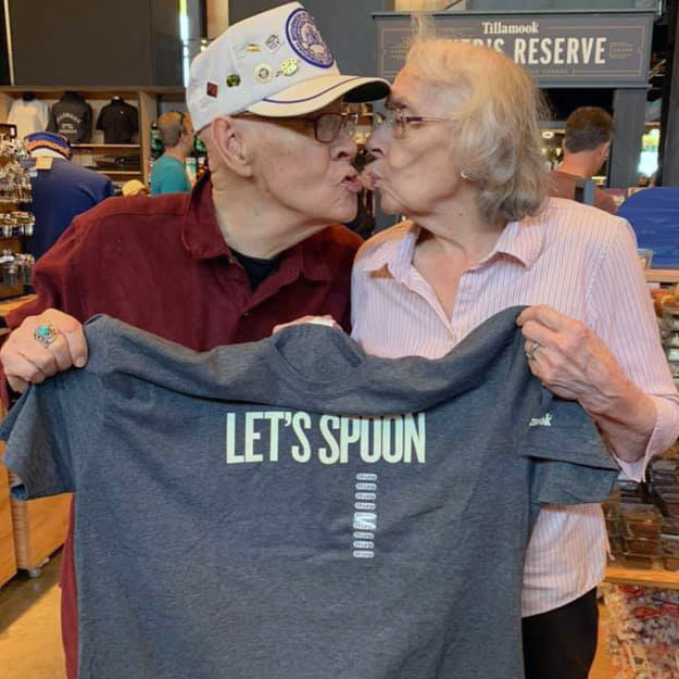 Two seniors kiss in their retirement living for assisted memory care people