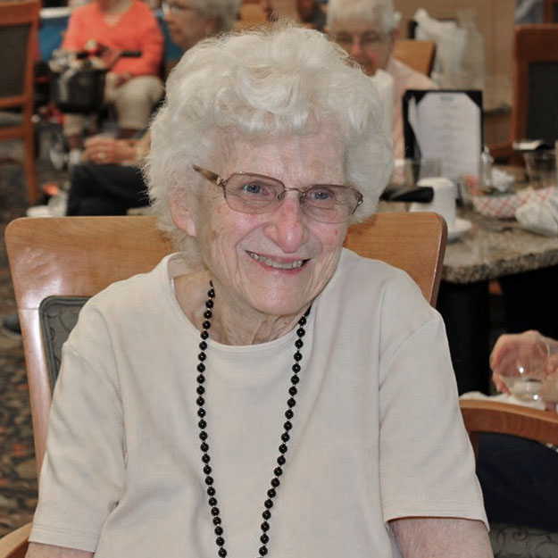 Happy senior smiling in her memory care living community for assisted living retirement