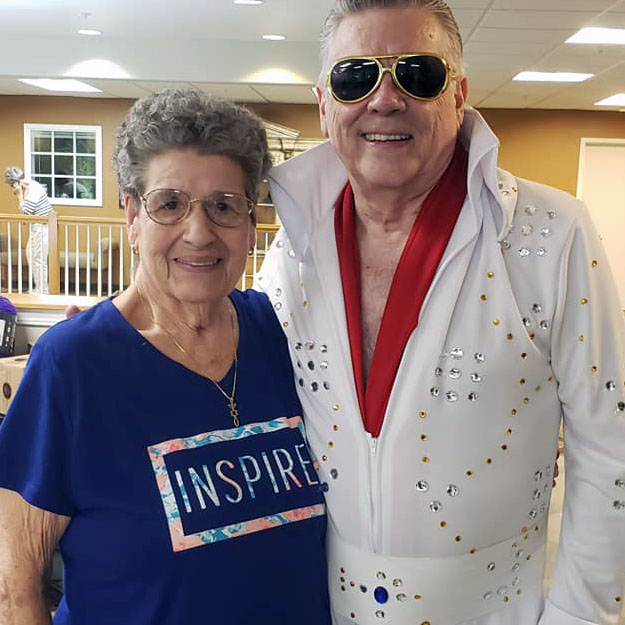 Senior lady and Elvis pose in assisted living community