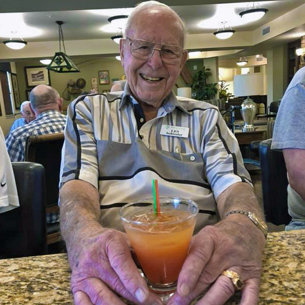 Senior man poses with drink in his assisted living community