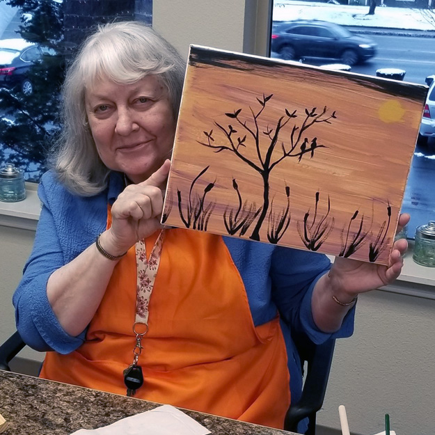 Senior woman in her retirement community holds up her painting art