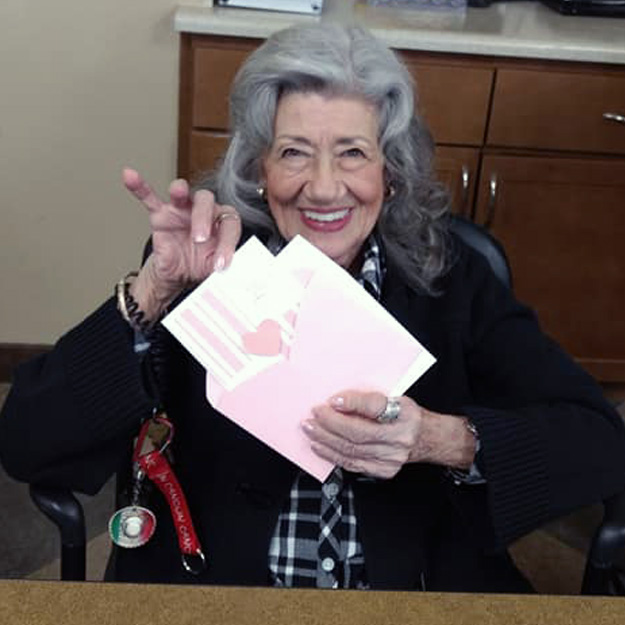 Happy senior woman with art card in independent living community