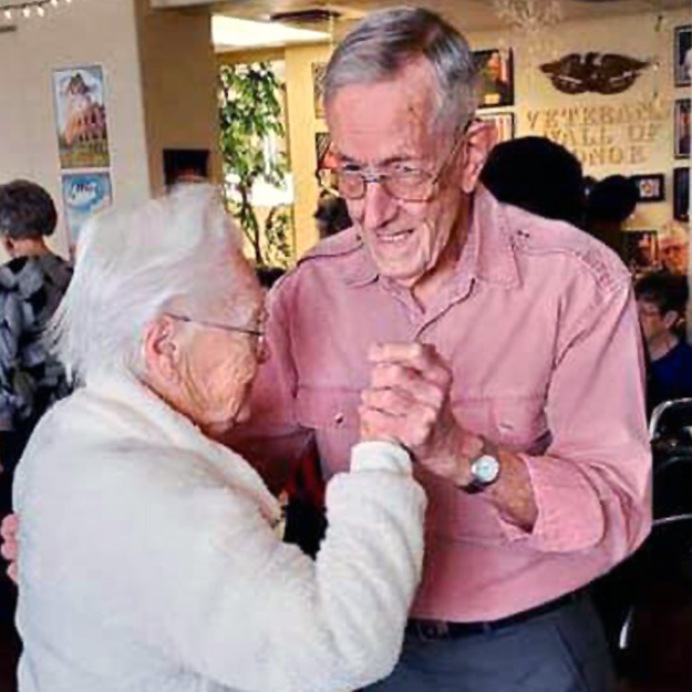 Two seniors enjoy a dance in their memory care community