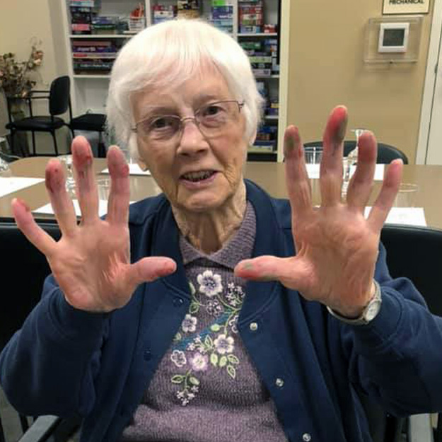 Senior showing her hands in memory care