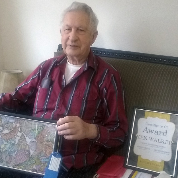 Senior man with award in his memory care community