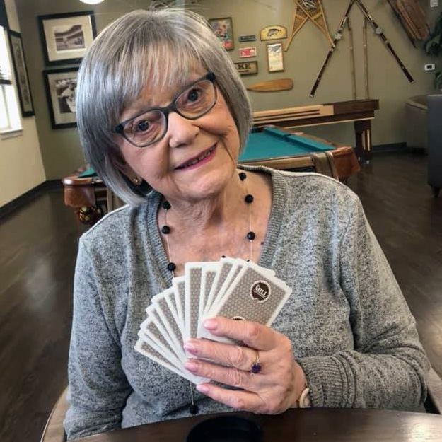 Senior playing cards in her retirement