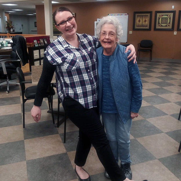Two senior friends embrace and laugh in assisted living