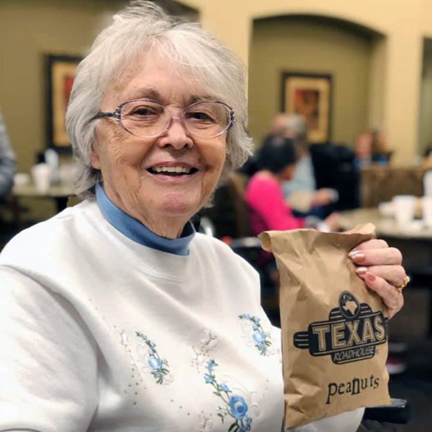 Senior woman holds bag in assisted living