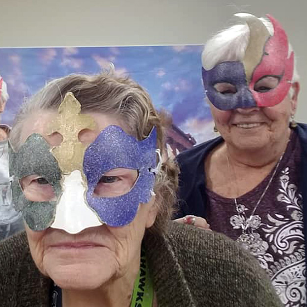 Two seniors wear masks in their independent living community