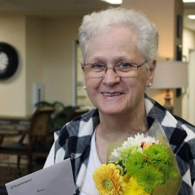 Smiling woman with flowers in assisted living community