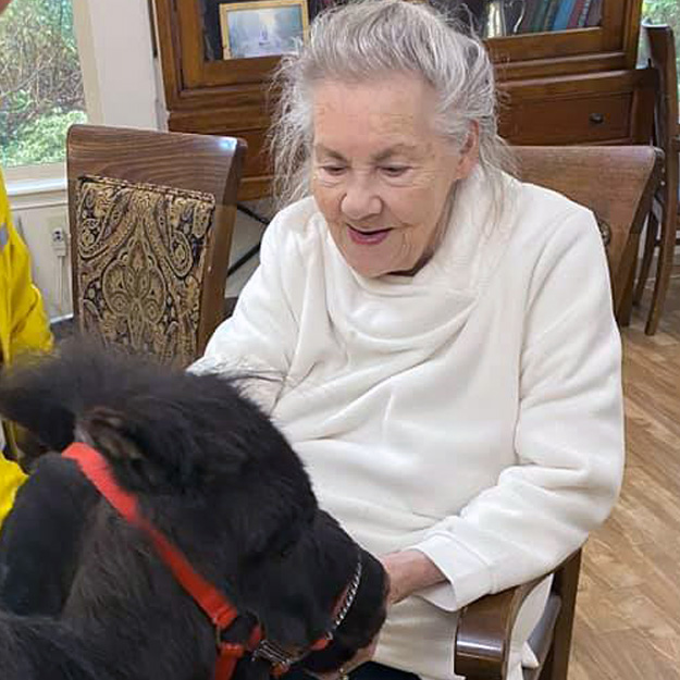 Memory care resident in retirement living community with horse