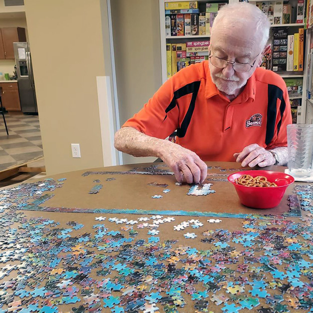 Senior man does a puzzle in independent living community