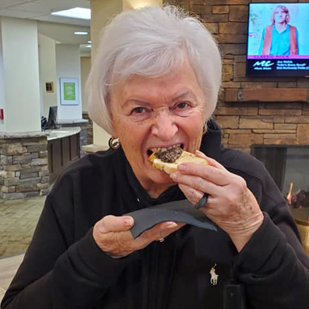 Senior woman eats dining perfected food in assisted living