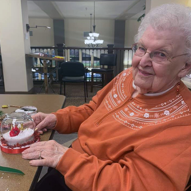 Happy senior does crafts in assisted living community