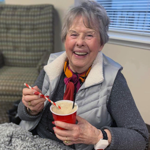 Laughing senior woman holds a drink in her assisted living community