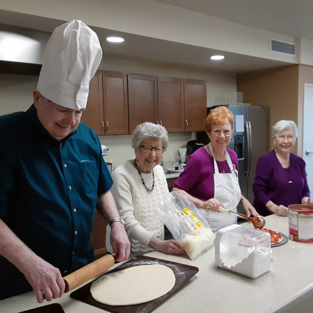 Group of seniors enjoy cooking in their memory care community